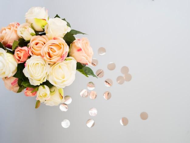 花の組成紙吹雪と薄紙の背景に柔らかいピンクのバラ。
