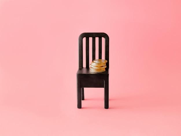 ピンクの背景にコインで椅子。クレジットまたはセールのコンセプト