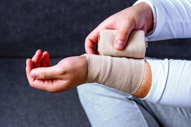 男がスポーツ用包帯で手を包帯します。スポーツにおける怪我と緊張