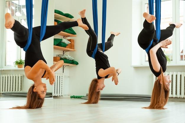 ストレッチ運動。黒い制服を着た若い女の子のグループは、ジムでストレッチトレーニングを行っています