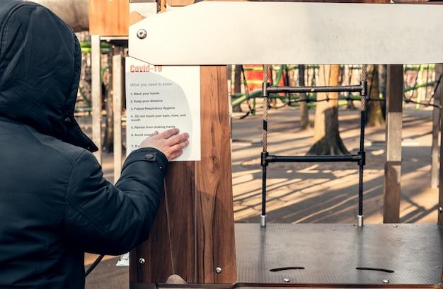 公園の空の遊び場に紙をぶら下げ