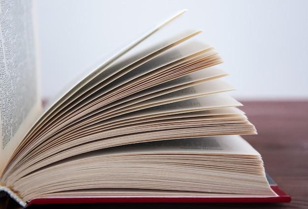 調子の木製テーブルの上に横たわる本を開いた。