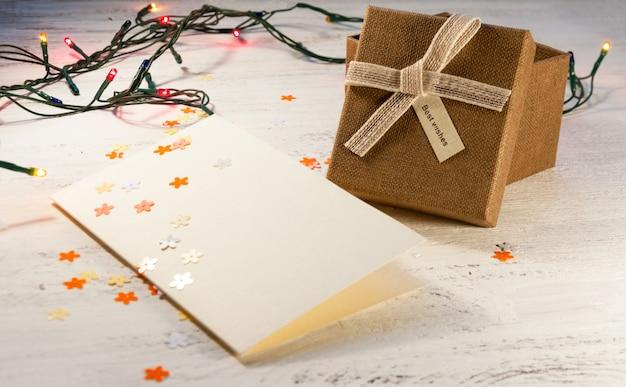 ライトと明るい背景に白紙のはがきとギフトボックスクリスマスガーランド。クリスマスプレゼント。