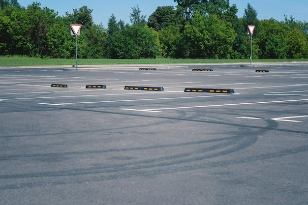 夏の駐車場の車のための現代のゴム製障壁。アスファルトのタイヤトラック。
