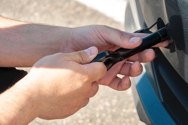 男が車の前でけん引用のフックを回転させます。車の故障とけん引。