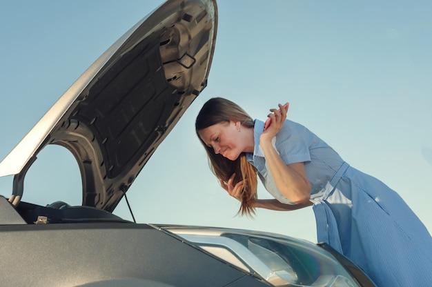オープンフードで壊れた車の近くの若くて美しい女の子。車の問題は、開始されません、動作しません。