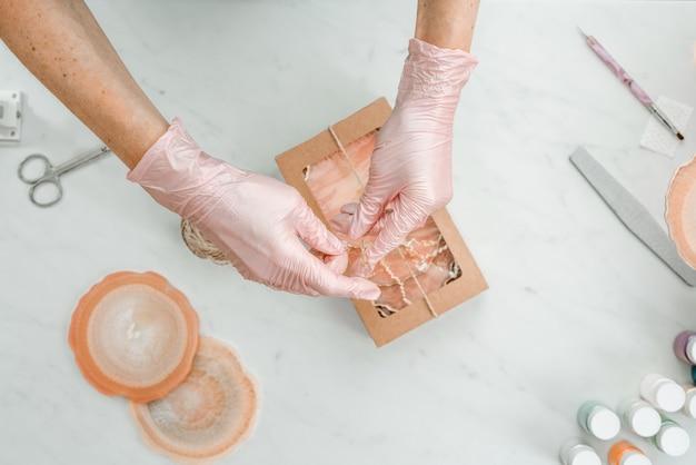 創造性と工芸品。若い女の子が樹脂からコースターを作成しています。ギフト包装。装飾的な包装。ビジネスのためのアイデア。在宅勤務、在宅勤務。アートコースター。