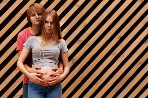 Молодая пара мужа обнимает красивую беременную жену, стоящую возле полосатой стены.