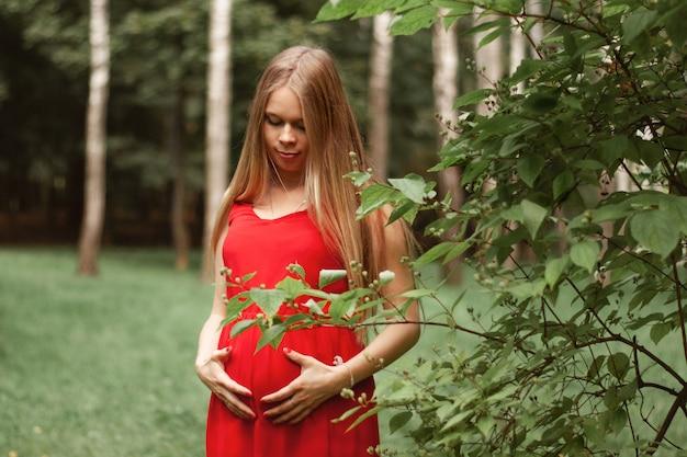 Молодая красивая и счастливая беременная девушка гуляет в парке. держит руки на животе. здравоохранение.