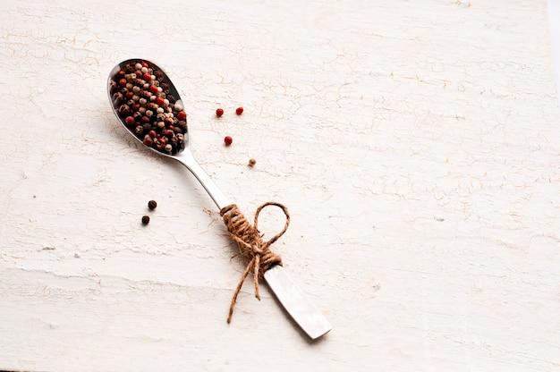 惨劇によって描かれたハンドル付きのスプーンでマルチカラーのコショウの種。
