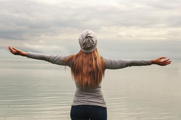 カメラに背を向けて美しい少女が海岸に立っています。手を挙げろ。日没。ヨガのクラス。
