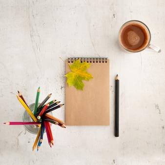 色鉛筆、乾燥した葉、紙。テキストのフレーム。上からの眺め。秋の組成物。トレーニング。