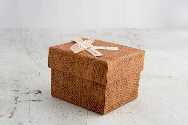 Подарочная коробка на светлом фоне. декорации к празднику. поздравления, новый год, день рождения.