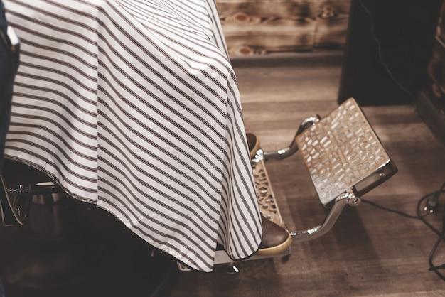 理髪店で髪を洗うための椅子。理髪店のインテリア。残忍な場所。金属張りの革張りのアームチェア。セレクティブフォーカス。