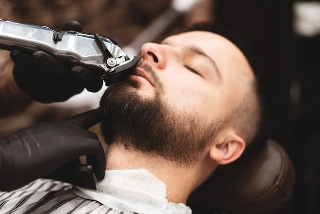 理髪店で危険なカミソリでひげを剃る。理髪店のひげのケア。乾燥、切断、ひげの切断。セレクティブフォーカス。