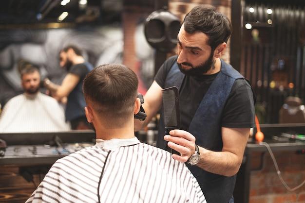 理髪店の散髪ヘッド。理容師は、クライアントの頭の毛をカットします。男性用のヘアスタイルを作成するプロセス。理髪店。セレクティブフォーカス。