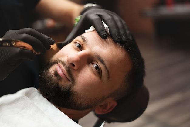理髪店で危険なカミソリでひげを剃る。