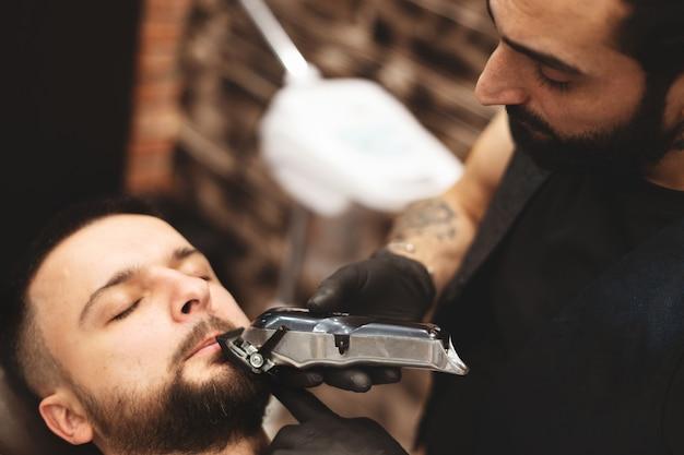 Брить бороду в парикмахерской опасной бритвой.