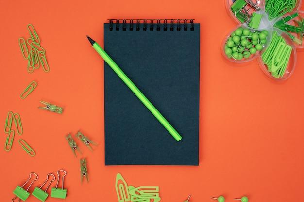 教育的構成、文房具。緑の文房具と黒の黒のノートブック