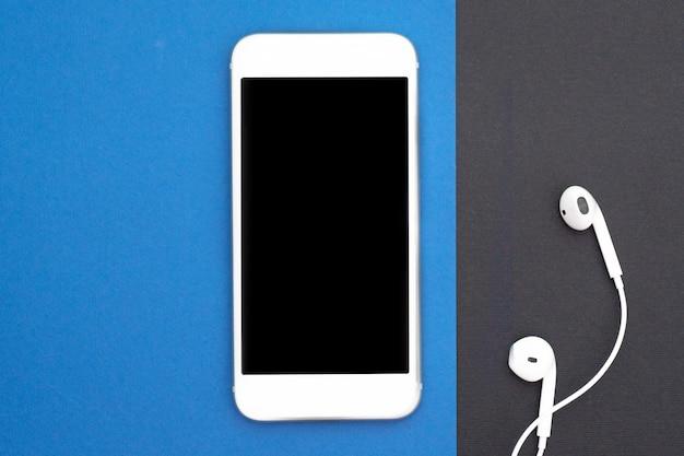 Музыка, гаджеты, меломан. белый смартфон на черном и синем