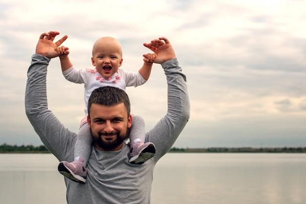 父親の首にかかった子供。水の近くを歩きます。赤ちゃんとパパの空を背景。