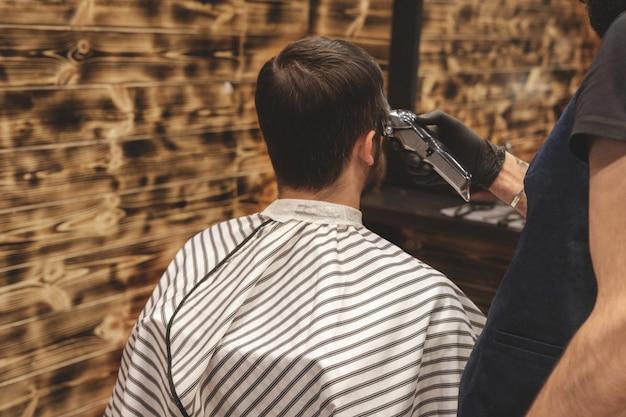 理髪店の散髪ヘッド。理容師はクライアントの頭の毛を切る