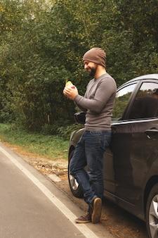 空の道で車の近くのハンバーガーを食べる若い男。旅行中の食べ物。外出先での食事。秋の旅行。ファストフード。