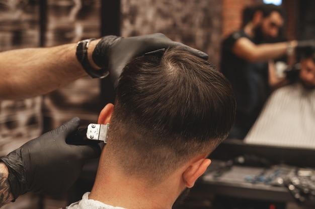 理髪店の散髪ヘッド。理容師は、クライアントの頭の毛を切ります。男性用のヘアスタイルを作成するプロセス。理髪店。セレクティブフォーカス。