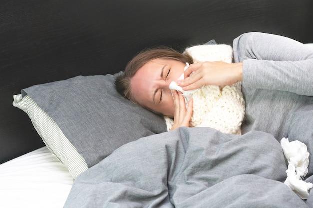 疾患。ホームトリートメント。女性は自宅で病気で、鼻水とインフルエンザがあります。暖かい服を着て、毛布で覆われています。ナプキン、鼻水に彼女の鼻を吹きます。感染症、伝染病、菌キャリア