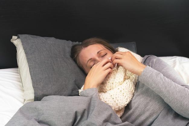 疾患。ホームトリートメント。女性は自宅で病気で、鼻水とインフルエンザがあります。暖かい服を着て、毛布で覆われています。