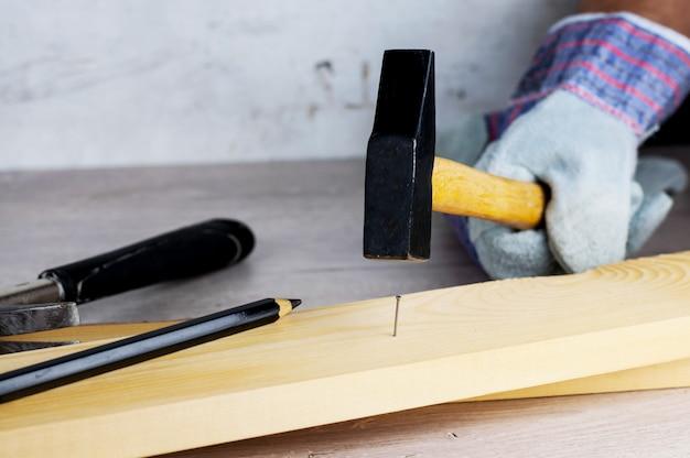 家の建設や修理に取り組んでください。独立した更新、改修。作業用手袋とハンマーを使用する。
