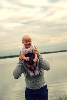 Ребенок на шее у отца. прогулка у воды. младенец и папа против неба.