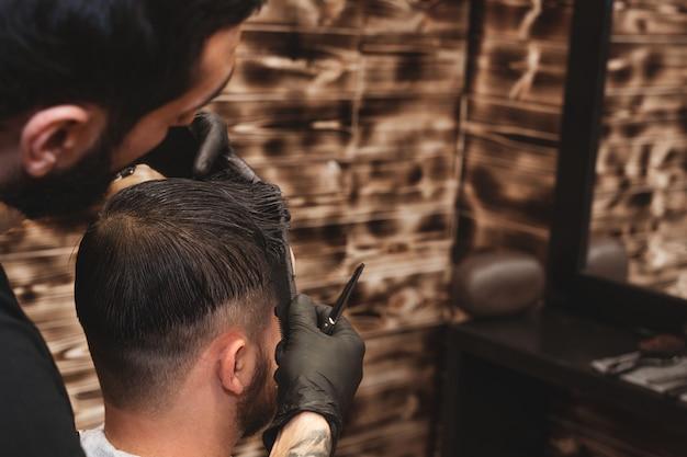Стрижка головы в парикмахерской. парикмахерская стрижет волосы на голове клиента. процесс создания прически для мужчин. парикмахерская.