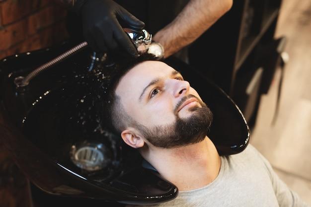 В парикмахерской мужчина моет волосы. парикмахер моет своего клиента. вымойте волосы и бороды после стрижки. личная гигиена.