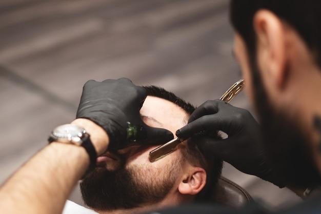 理髪店で危険なカミソリでひげを剃る。理髪店のひげのケア。乾燥、切断、ひげの切断。