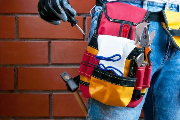 道具のためのベルトの道具。ビルダーはドライバーを握ります。セレクティブフォーカス