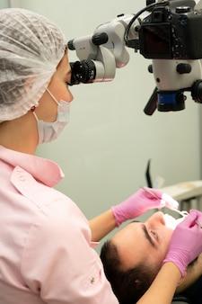Молодой женский стоматолог смотрит через профессиональный микроскоп в стоматологической клинике. современное оборудование в стоматологии.