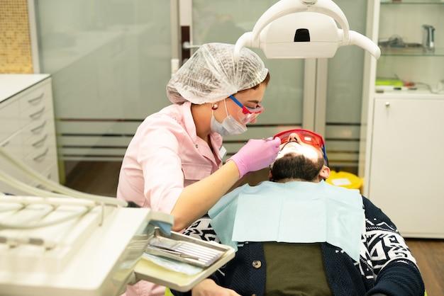 Стоматолог молодая женщина лечит больного мужчину. врач использует одноразовые перчатки, маску и шапочку.