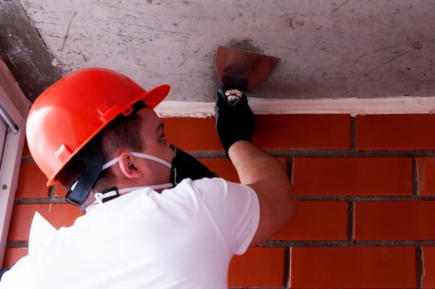 Мужчина в шлеме и респираторе выполняет малярные работы на бетонном потолке