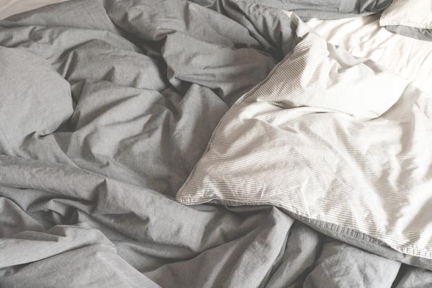 しわくちゃのグレーの生地。朝のベッド。広げたベッド。
