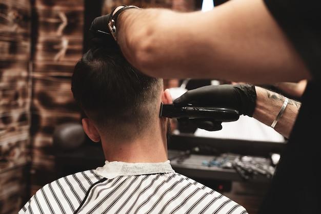 理髪店の散髪ヘッド。理容師は、クライアントの頭の毛をカットします。男性用のヘアスタイルを作成するプロセス。理髪店。