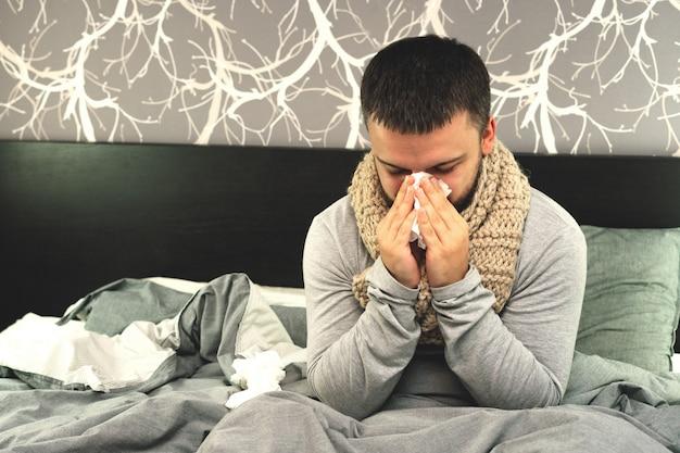 疾患。自宅で応援してください。若い男は病気で、自宅で治療