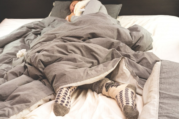 疾患。ホームトリートメント。インフルエンザと風邪。若い女性は自宅で病気、鼻水、インフルエンザにかかっています。