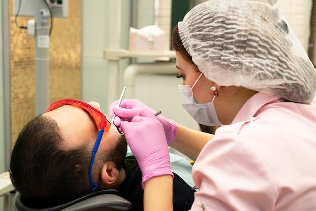 若い歯科医は患者を扱います