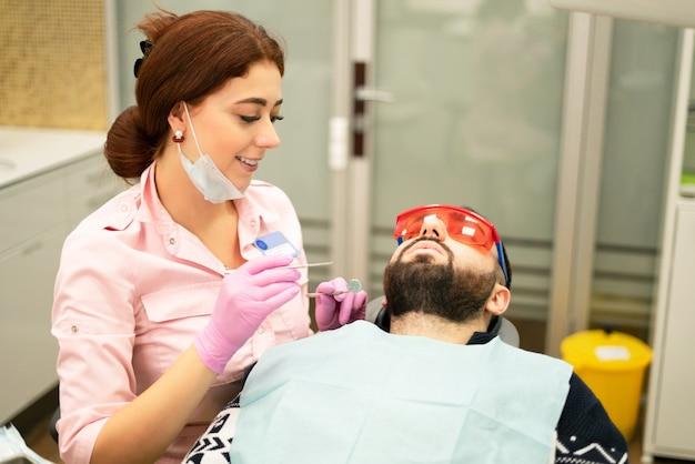 歯科医の若い女性は、患者を男を扱います。医師は使い捨て手袋、マスク、帽子を使用します。歯科医は患者の口で働き、プロのツールを使用します