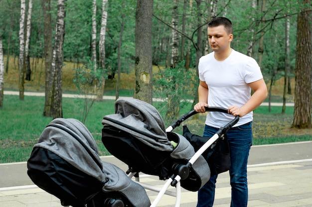 Папа гуляет в парке с двумя маленькими детьми