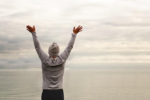 若い男が海岸に立っています。後ろからの眺め。ヨガのクラス。手を挙げた。自由と達成。