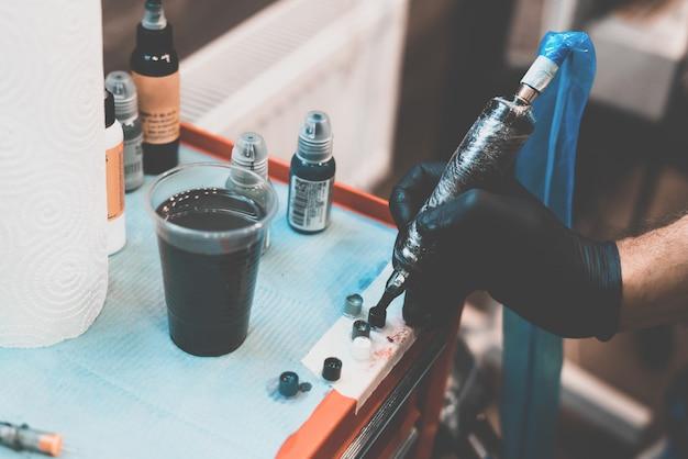 タトゥーサロン。タトゥーマシンとテーブルの上の入れ墨の準備された塗料。塗料を硬化させるプロセス。クローズアップ、彩色、彫師。