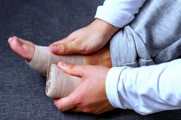 男がスポーツ用包帯で足を包帯します。スポーツにおける怪我と緊張