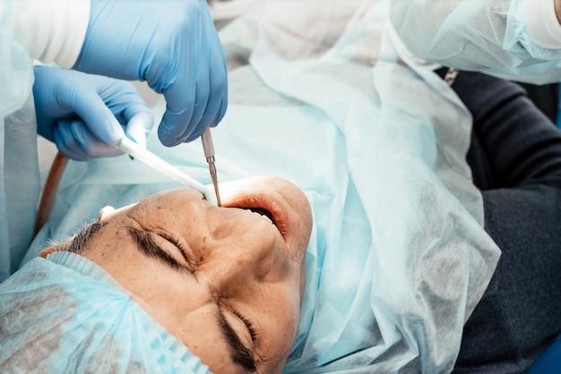 手術時の歯科医の椅子にいる患者。抜歯、インプラント。プロのユニフォームと歯科医の機器。